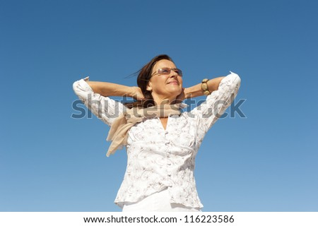 Attractive and happy middle aged woman relaxed and casual enjoying active retirement, isolated with blue sky as background and copy space. - stock photo