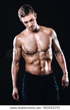Attractive and muscular athlete. Studio shot of young shirtless sportsman on black background