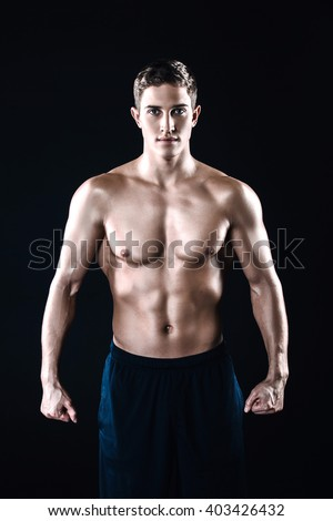 Attractive and muscular athlete. Studio shot of young shirtless sportsman on black background. Man looking at camera