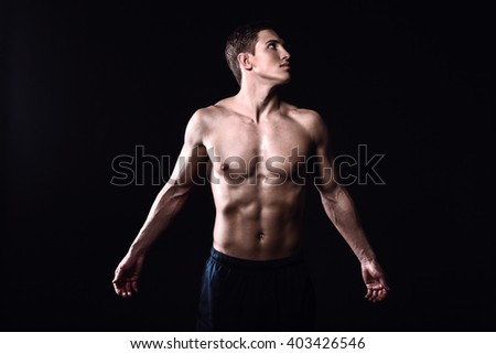 Attractive and muscular athlete. Studio shot of young shirtless sportsman on black background. Man with outstretched arms - stock photo
