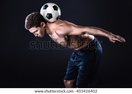 Attractive and muscular football player. Studio shot of young shirtless sportsman on black background. Man with football ball on back - stock photo