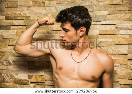 Attractive and muscular shirtless young man leaning against stone wall doing bicep pose - stock photo