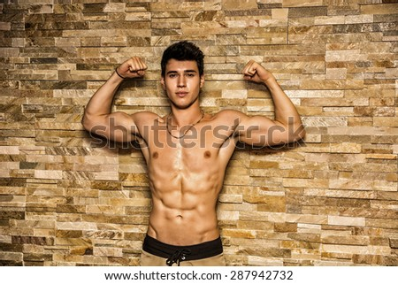 Attractive and muscular shirtless young man leaning against stone wall doing double bicep pose - stock photo