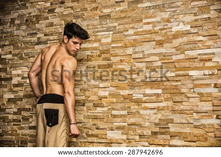 Attractive and muscular shirtless young man leaning against stone wall, seen from back - stock photo
