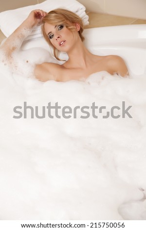 Attractive and sensuality blonde woman in bath relaxing. Closeup of young adult woman in bathtub bathing - stock photo