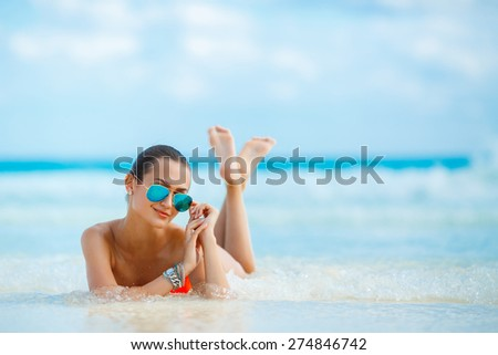 Attractive and sexy girl on the beach. Young female enjoying sunny day on tropical beach. Beautiful girl sunbathing under summer sun lying in sand on beach with blue water - stock photo