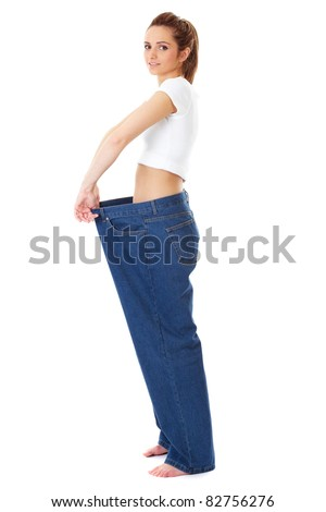 attractive and young female shows her old huge pair of jeans, diet concept, studio shoot isolated on white - stock photo