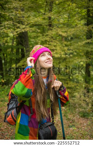 Attractive and young traveler with backpack standing with green forest on background, adventure travel and discovery