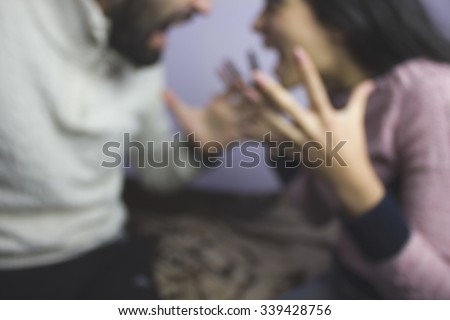 attractive angry couple fighting and shouting at each other - stock photo