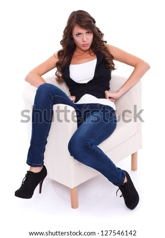 Attractive angry woman sitting in armchair, studio shot - stock photo
