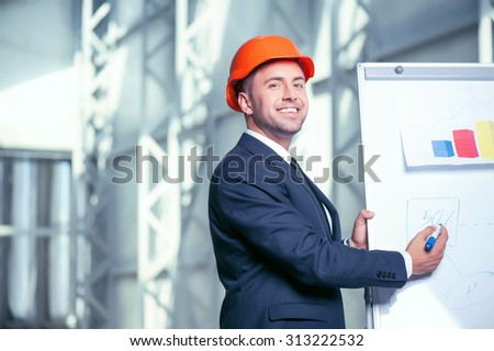 Attractive architect is drawing sketches of construction. He is standing near a board of a blueprint and smiling. He is looking at the camera with joy. Copy space in left side - stock photo