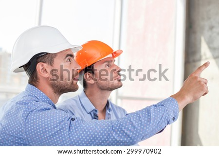 Attractive architect is explaining to a foreman the main concepts of construction. He is pointing his finger forward. They are looking at this place with attention and seriousness - stock photo