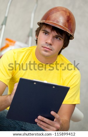 Attractive architector in helmet writing notes - stock photo