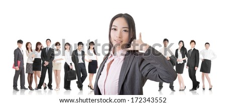 Attractive Asian business woman give you a phone call sign and stand in front of her team. - stock photo