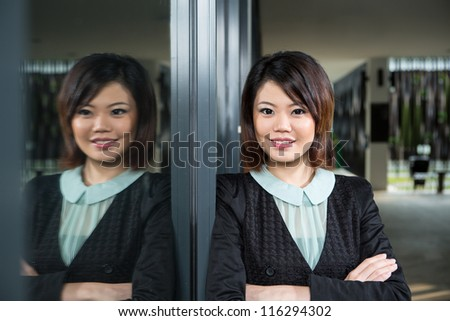 Attractive Asian business woman standing with her arms folded. - stock photo