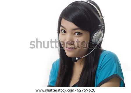 Attractive Asian business woman wearing headset and smiling - stock photo