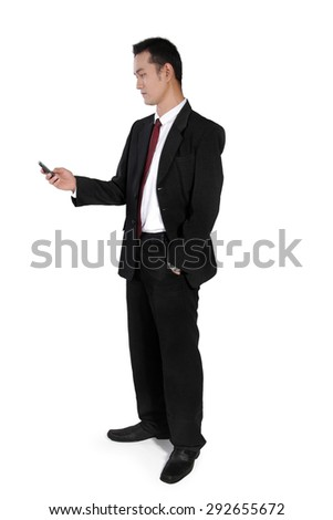 Attractive Asian businessman standing with one hand in pocket, checking on his mobile phone, full body shot, isolated on white background - stock photo