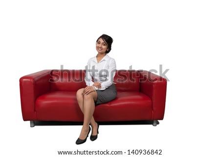 Attractive Asian businesswoman sitting on sofa - stock photo