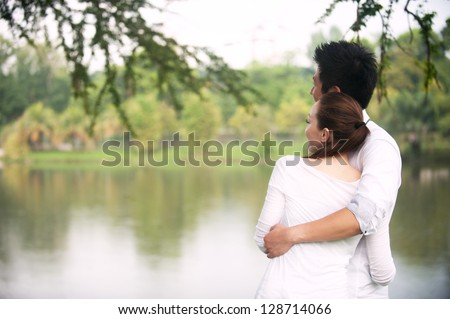Attractive Asian Couple enjoying lake view in park - stock photo