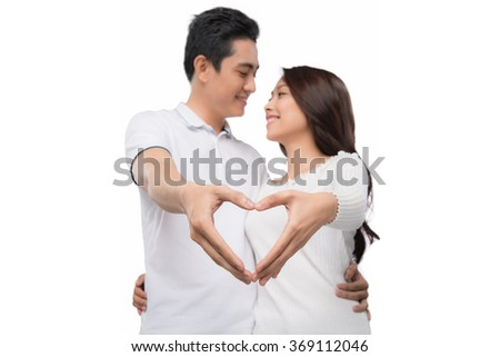 Attractive Asian Couple making a love symbol with hands. Focus on hands. Portrait of a guy and a girl forming a heart shape with their hands on white background - stock photo