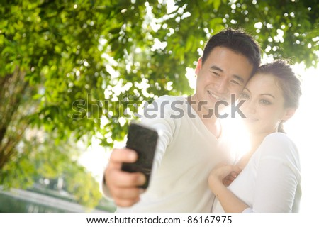 Attractive asian couple one smiling Taking Photographs in the park - stock photo