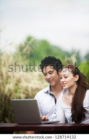 Attractive Asian Couple using a laptop in a park