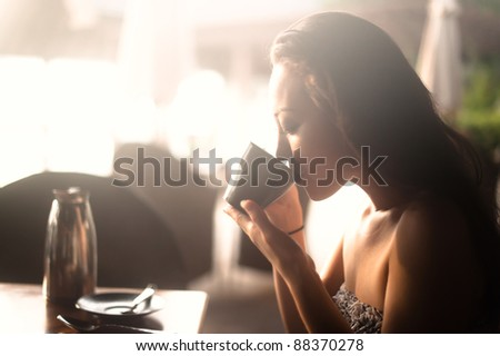 Attractive Asian Female drinking from a cup - stock photo