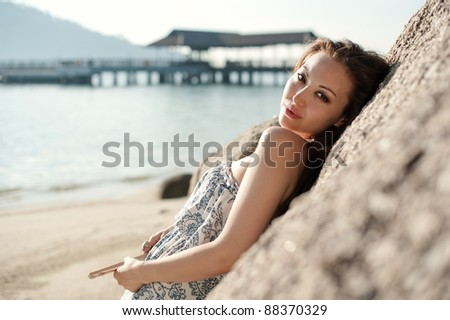 Attractive Asian Female leaning on a rock - stock photo