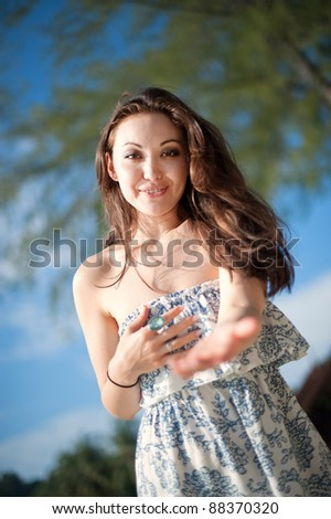 Attractive Asian Female reaching out with open hands - stock photo