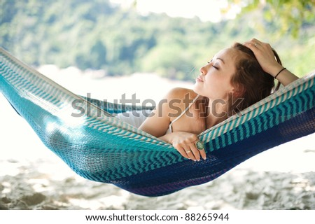 Attractive asian female relaxing on a hammock - stock photo