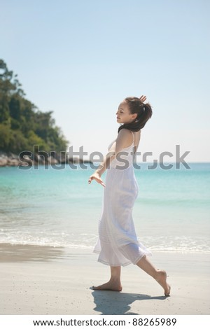 Attractive asian female running like flying on the beach - stock photo