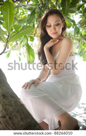 Attractive Asian Female sitting on a branch of a tree - stock photo