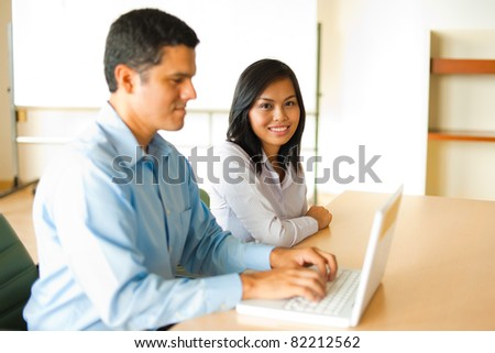 Attractive Asian female smiling, sitting at conference room desk in background looking at camera, meeting with Hispanic male businessman coworker working, looking at a laptop in office. Horizontal