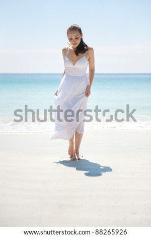 Attractive asian female strolling on the beach - stock photo