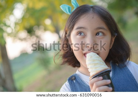 Attractive Asian girl enjoy eating soft ice cream