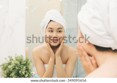 Attractive Asian girl enjoying soft skin of her face - stock photo