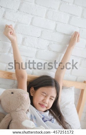 Attractive Asian girl stretching on the bed after wake up - stock photo