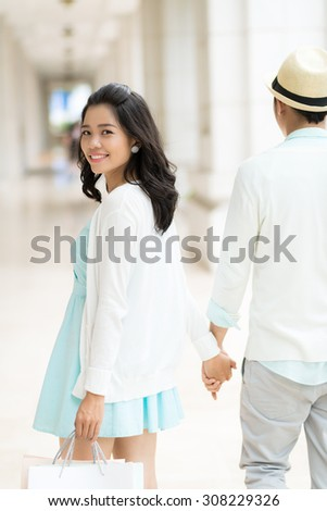 Attractive Asian girl with shopping bags turning back to look at the camera - stock photo