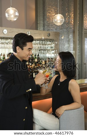 Attractive Asian man and woman toasting with their cocktails while at a bar. Vertical shot. - stock photo