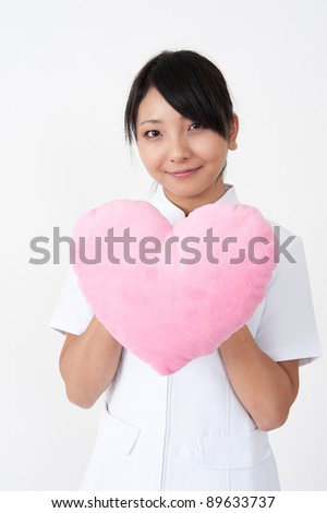 attractive asian nurse with symbol of heart - stock photo