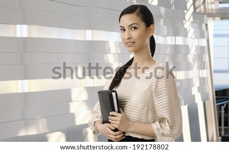Attractive asian secretary with personal business organizer. Elegant, smiling, looking at camera, standing at office lobby. Copyspace. - stock photo