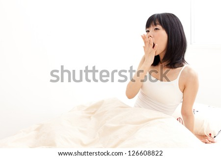 attractive asian woman awaking on the bed - stock photo