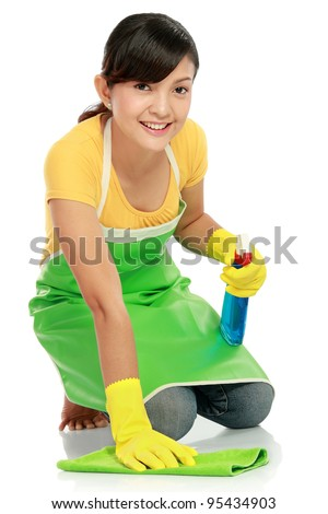 attractive asian woman cleaning the floor while kneeling at home - stock photo