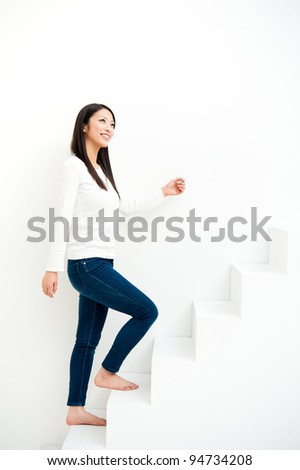 attractive asian woman going up on the stairs - stock photo