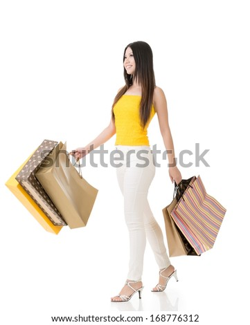 Attractive asian woman holding shopping bags and walking in studio. Full length portrait. Isolated on the white background. - stock photo