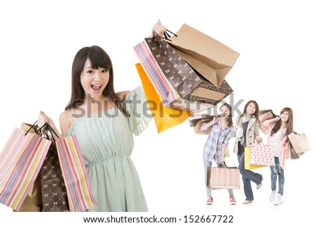 Attractive asian woman holding shopping bags in front of her friends. Isolated on the white background. - stock photo