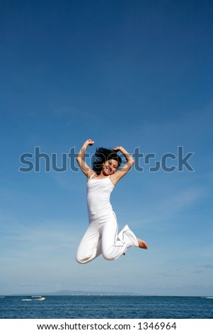 Attractive asian woman jumping at the beach - stock photo