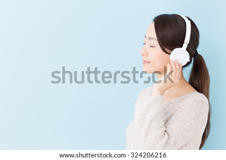 attractive asian woman listening music on blue background