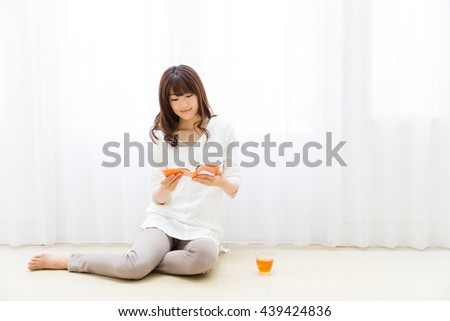 attractive asian woman reading book in the living room - stock photo