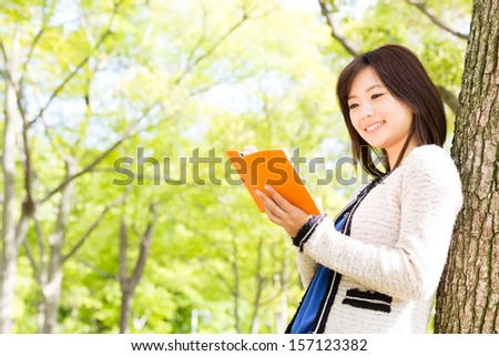 attractive asian woman reading book in the park